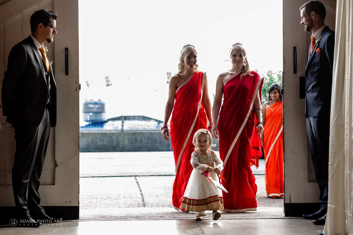 bridesmaids and flower girl entering the Black can at the entrance to trinity buoy wharf for the wedding