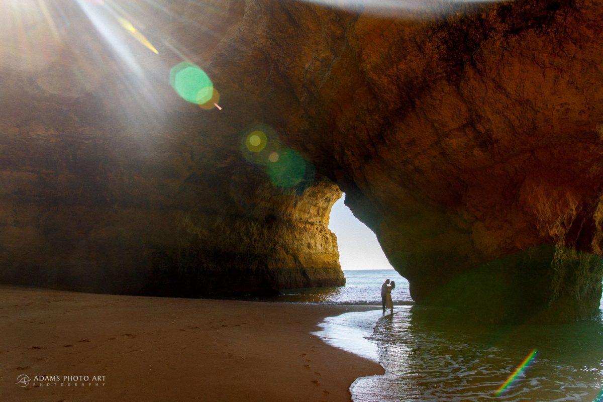 bride and groom are are posing in the cave in Algavre Praia de Benagil standin in the sea