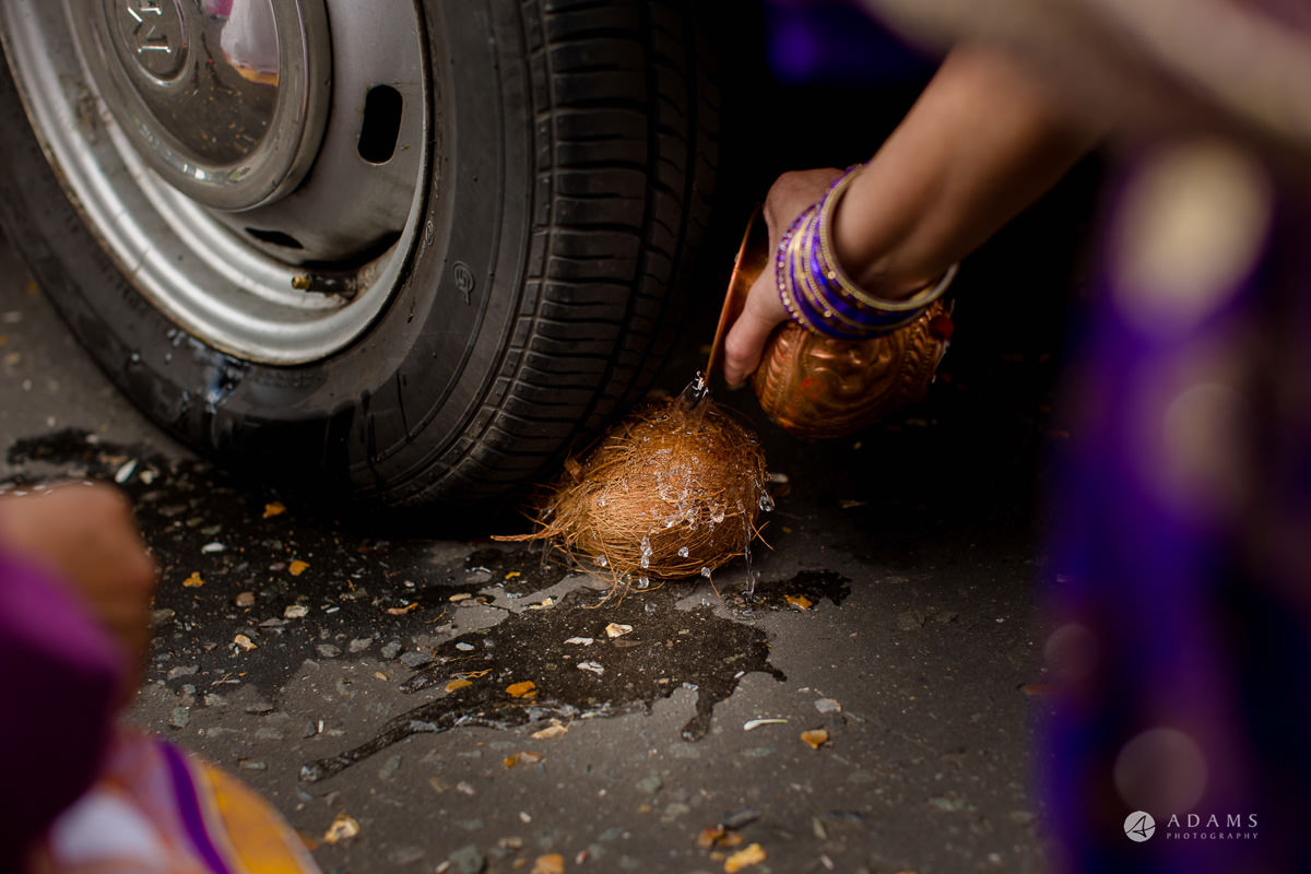 asian wedding coconut cracking by the car