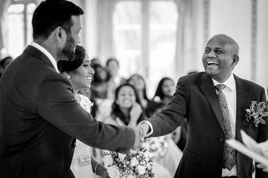 father of the bride shakes hand with groom art asian civil wedding