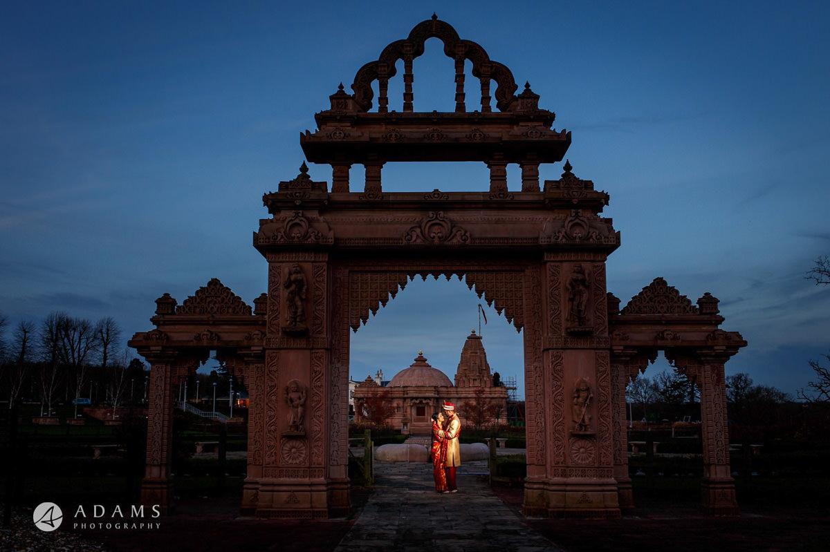 Hindu wedding posing by the temple