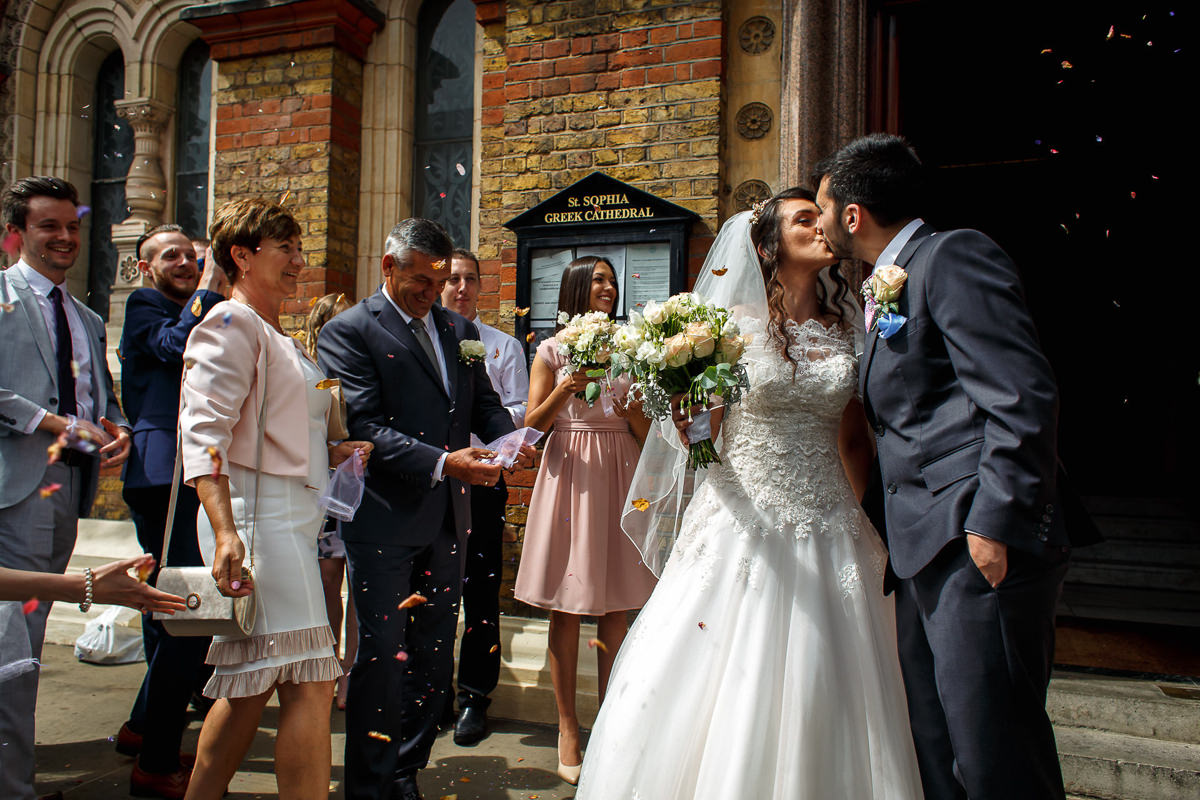 Greek Wedding bride and groom kiss in front of the Greek Orthodox Church