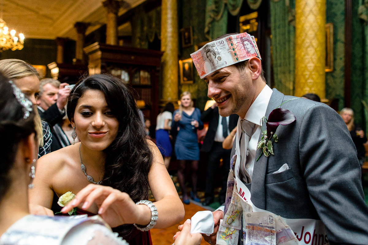 Greek Wedding bridesmaid pins the money on the bride