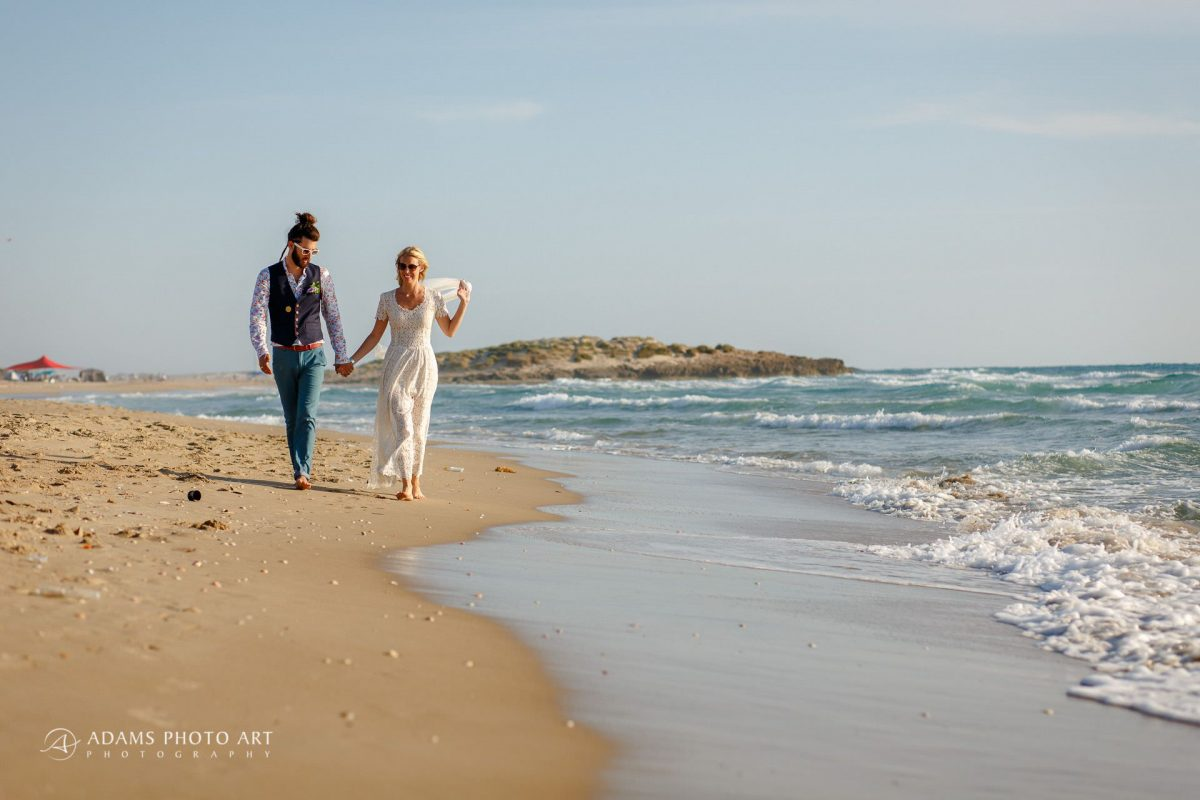 destination wedding photographer shooting a married couple walking along side the sea shore