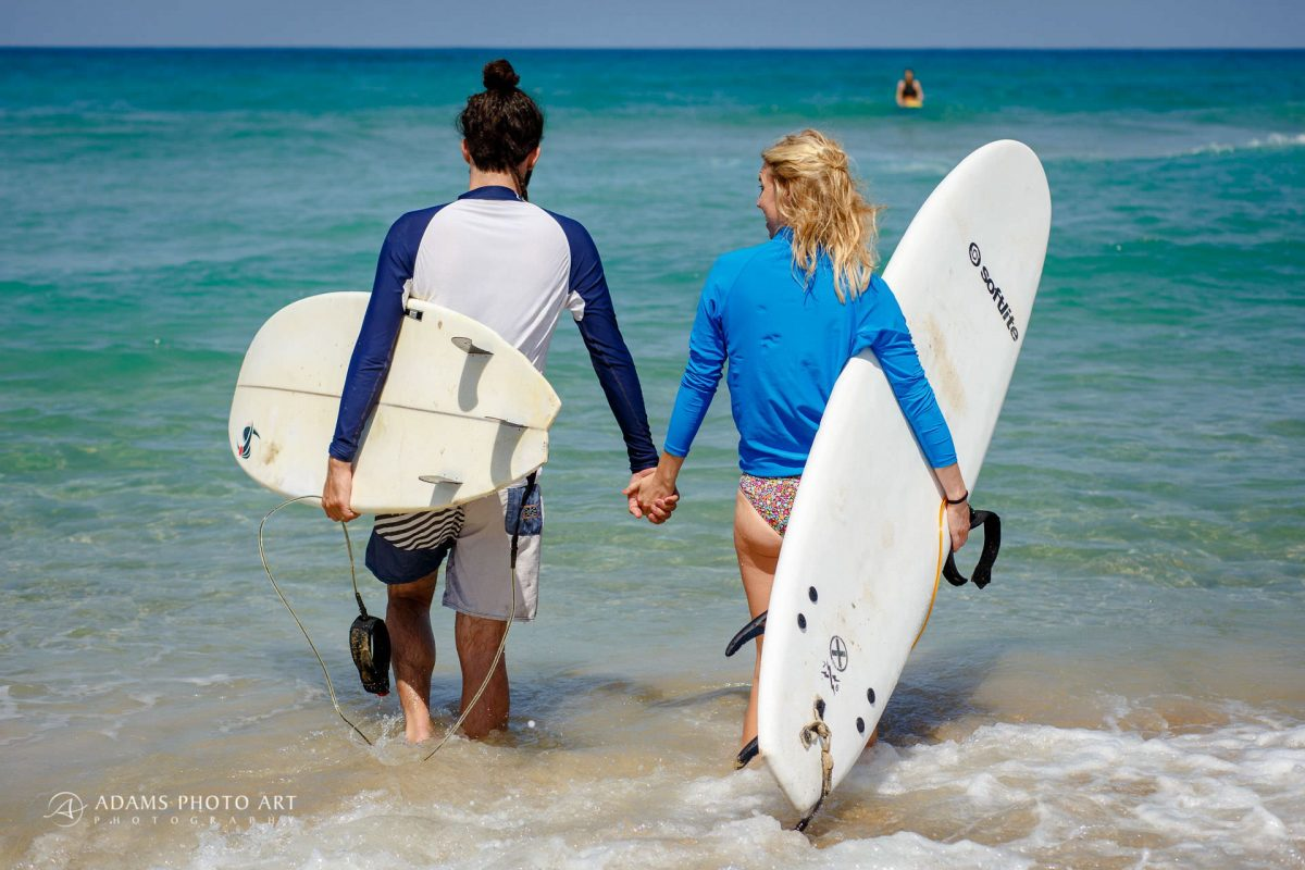 bride and groom are going to surf in the sea after they had their beach destination wedding ceremony