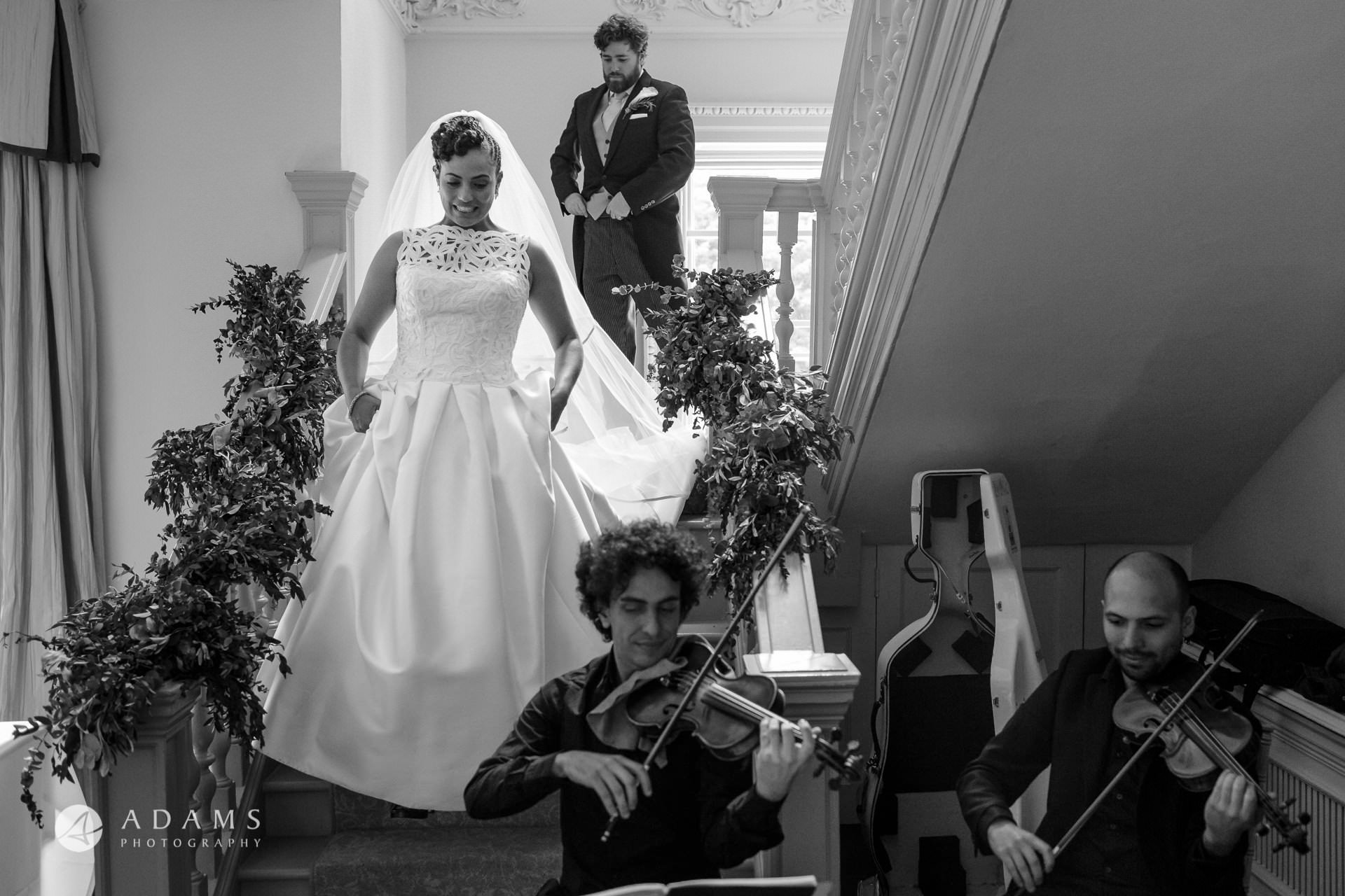 married couple walking down the stairs while the quartet is playing music at Morden Hall