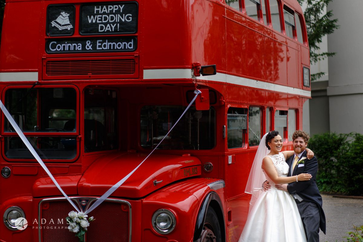 the married couple is posing by the red route-master bus in front of Morden Hall