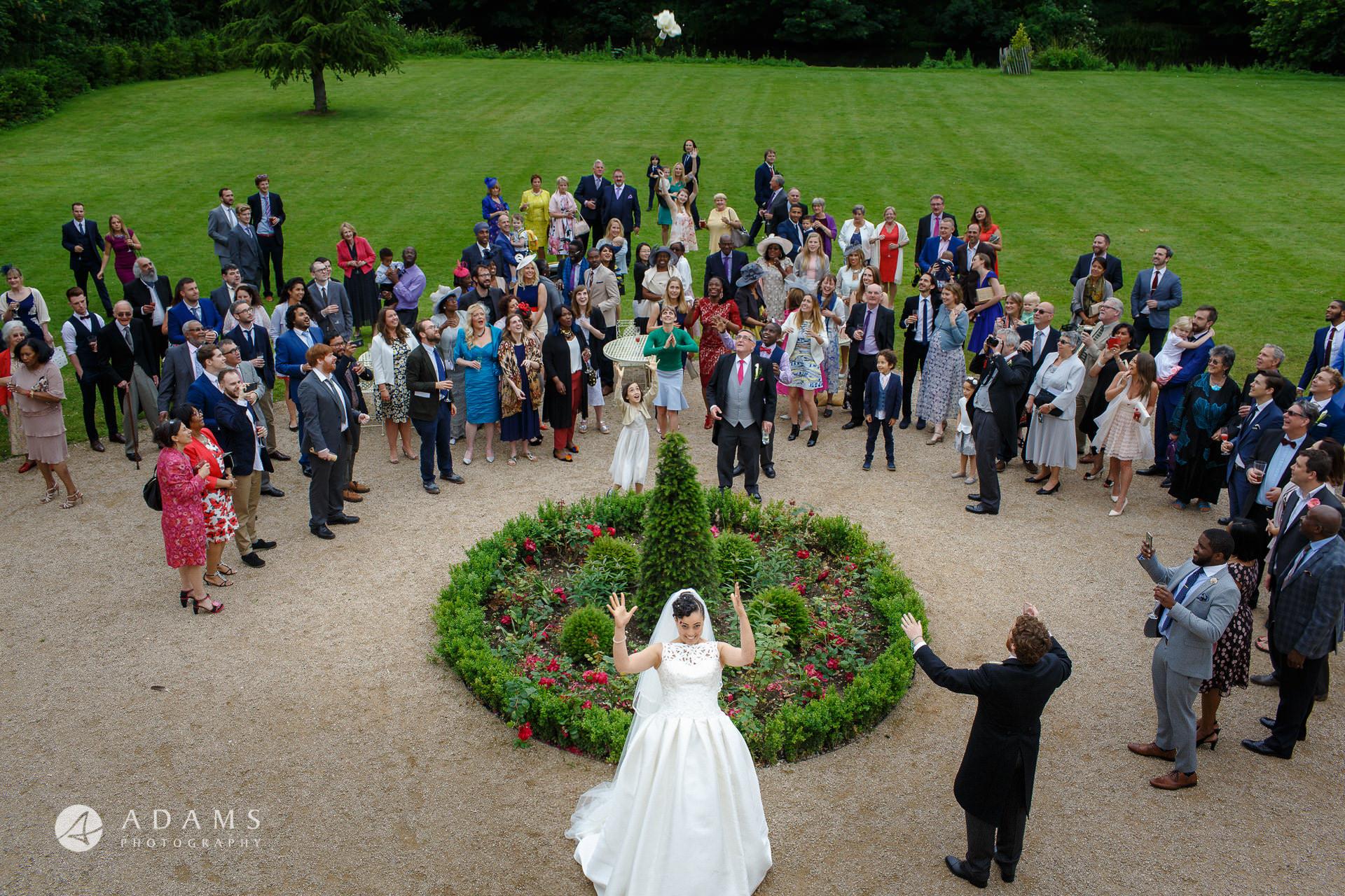 Morden HallWedding Morden Hall wedding photographer shooting throwing a bouquet at Morden Hall