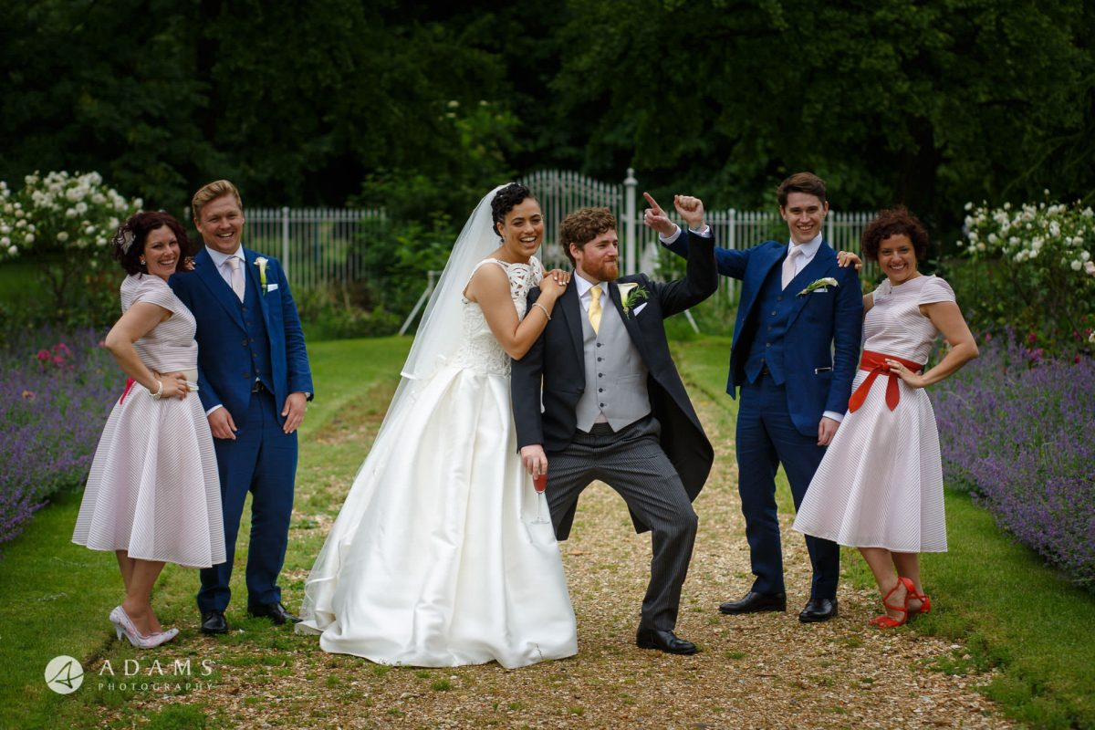 groom and bride and best-man and bridesmaids are posing in front of Morden Hall