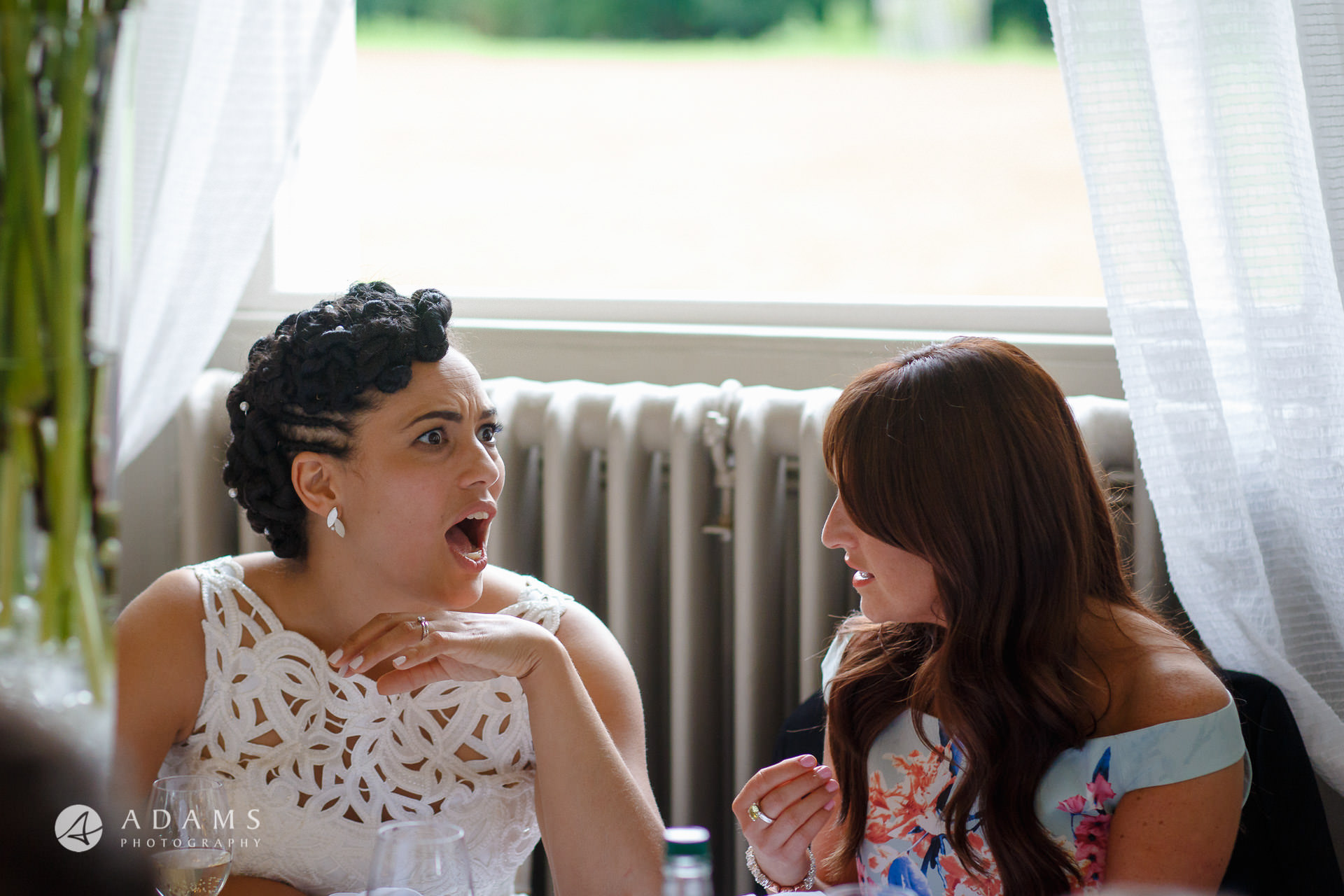 bride laughing while talking to her friend during the diner at Morden Hall