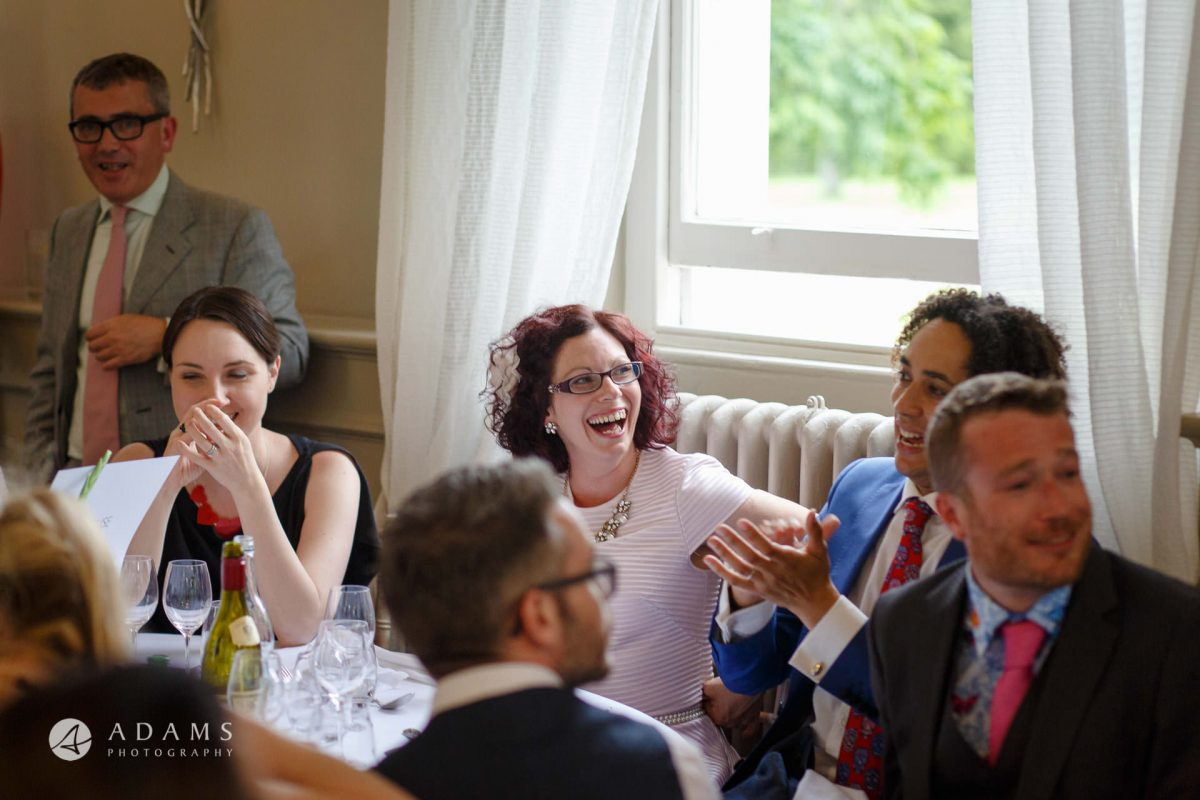 guest are laughing during dinner reception at Morden Hall