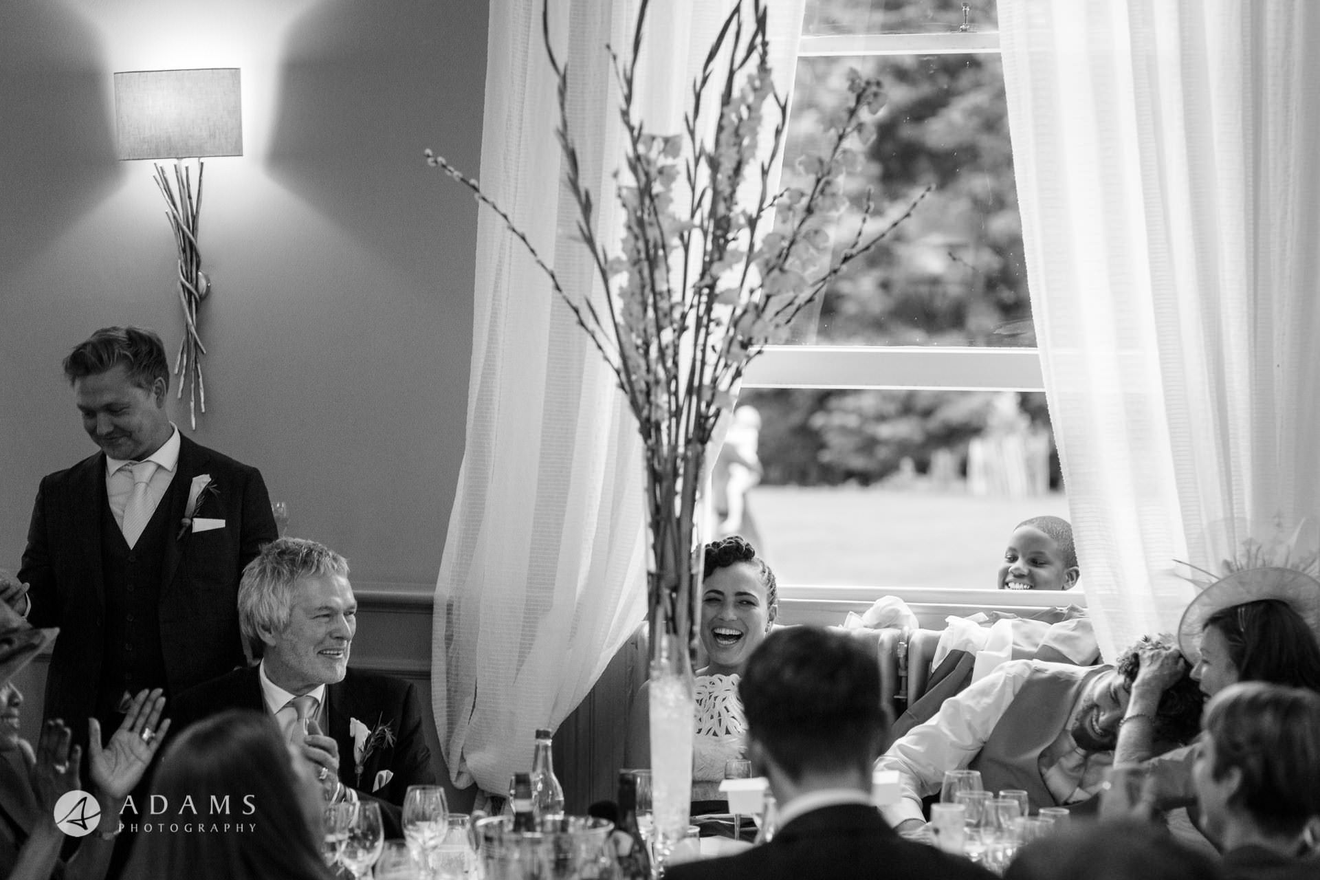 Morden HallWedding married couple and the guests are laughing during the dinner at Morden Hall