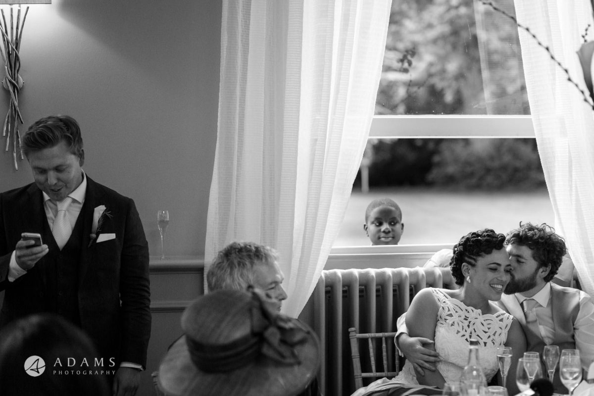a boy is looking through the window at the married couple during the speeches at Morden Hall