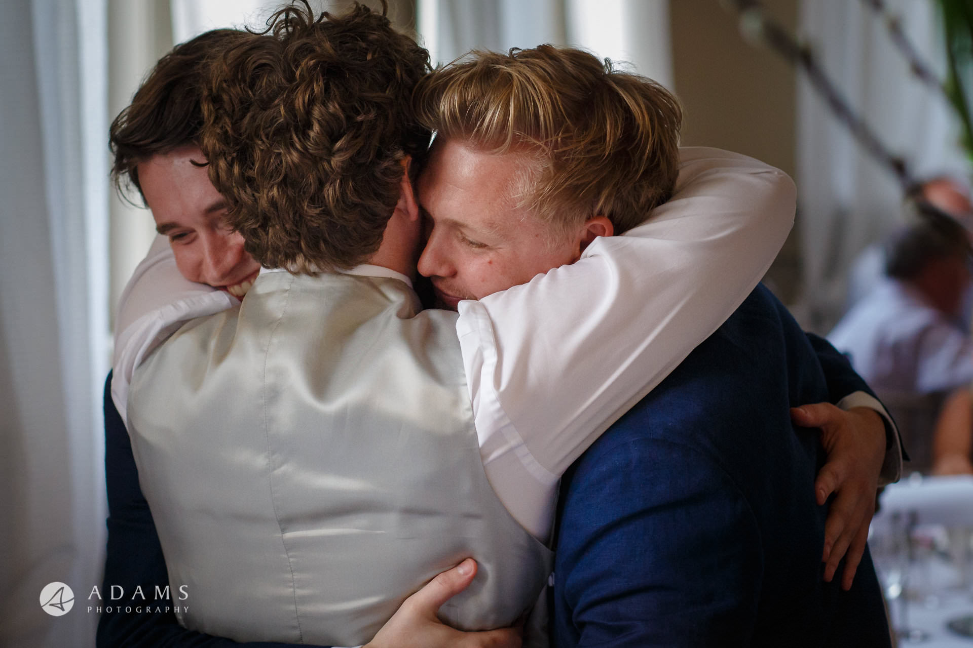 Morden Hall wedding photographer shooting the groom hugging two best men