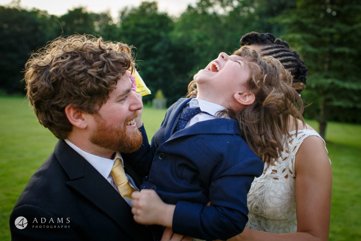 bride and groom hold a boy in their hand at Morden Hall wedding