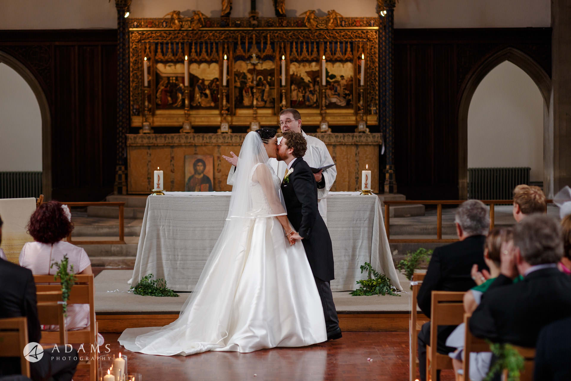 Bride and Groom having their first kiss at the alter at st Mary of Eton church in hackney wick during their wedding ceremony