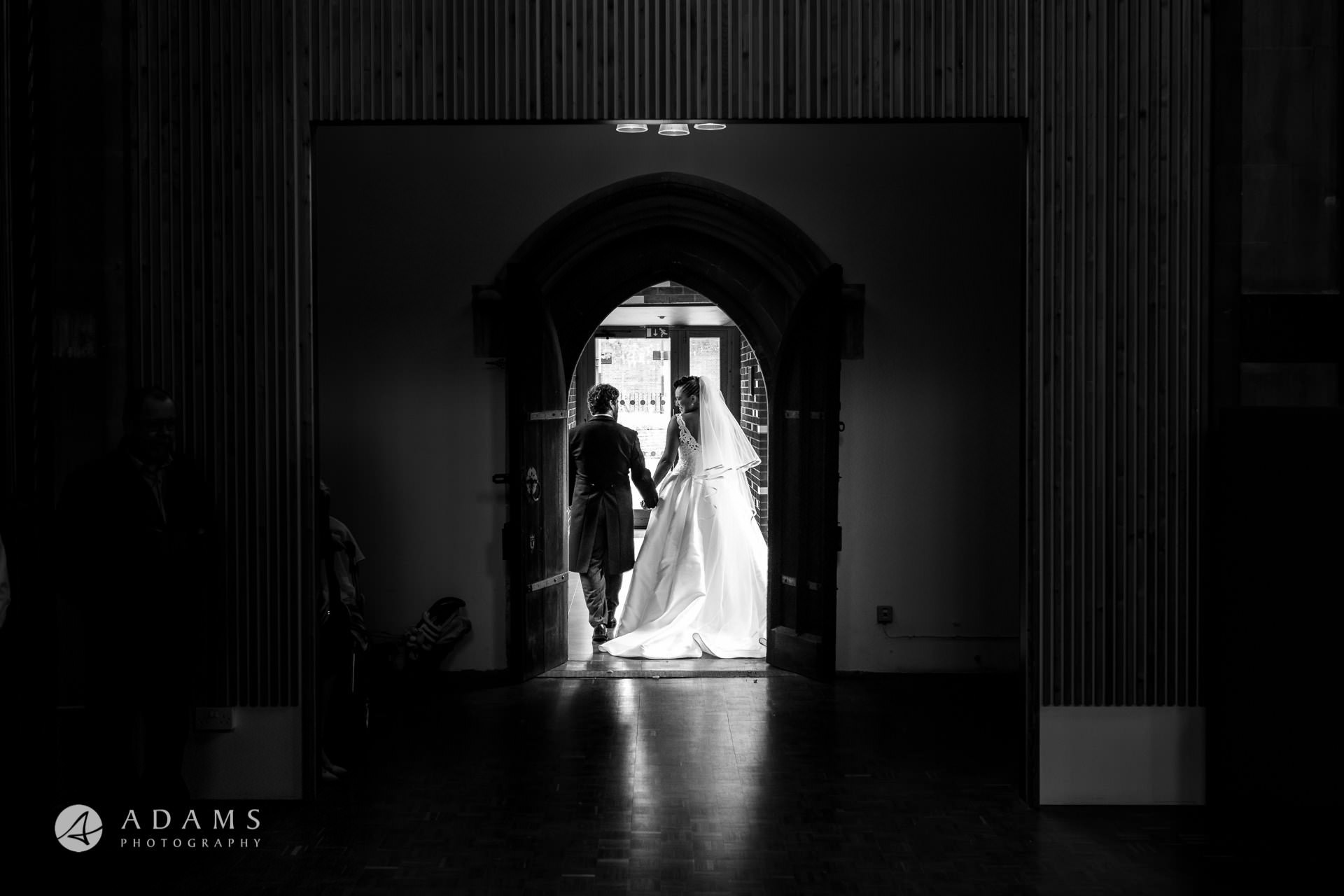 Bride and Groom hiding themselves at st Mary of Eton church in hackney wick during their wedding ceremony
