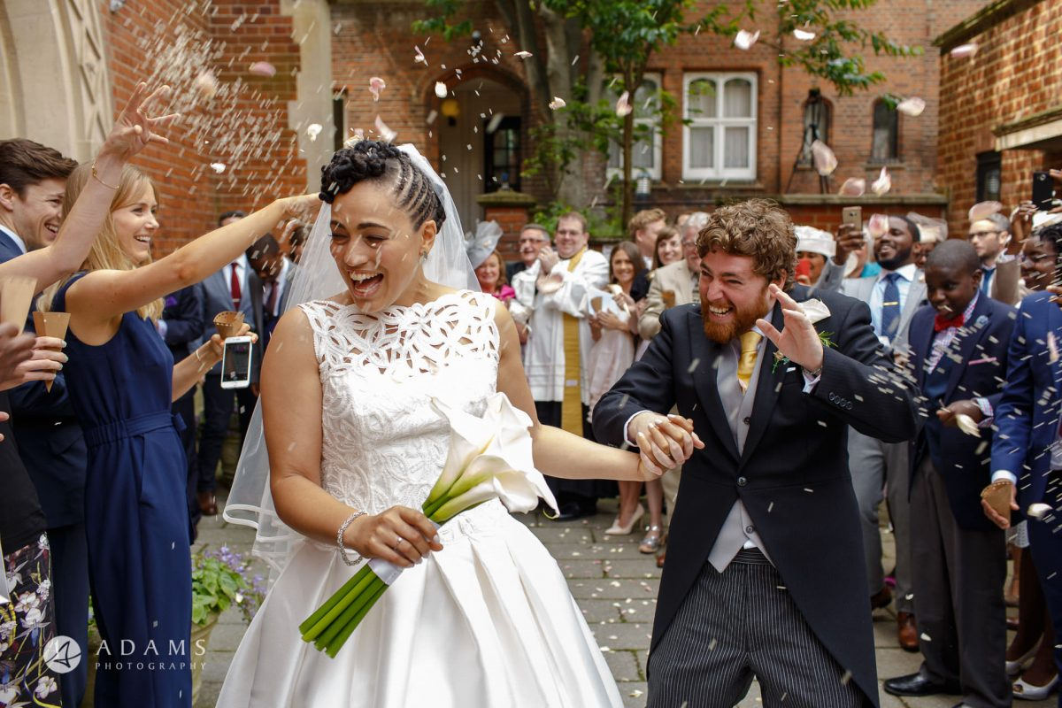 guests are throwing confetti at newly wed couple st Mary of Eton church in hackney wick after their wedding ceremony