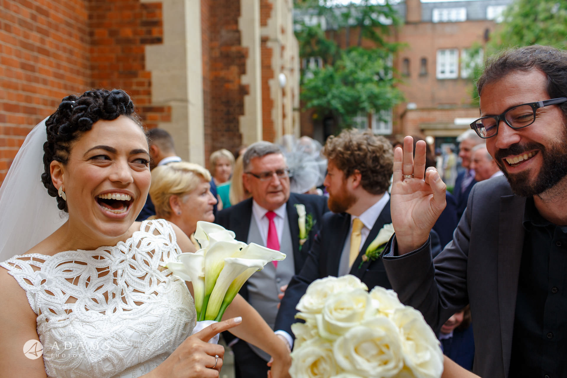 bride is being greeted by a guest after their wedding ceremony at st Mary of Eton church in hackney wick