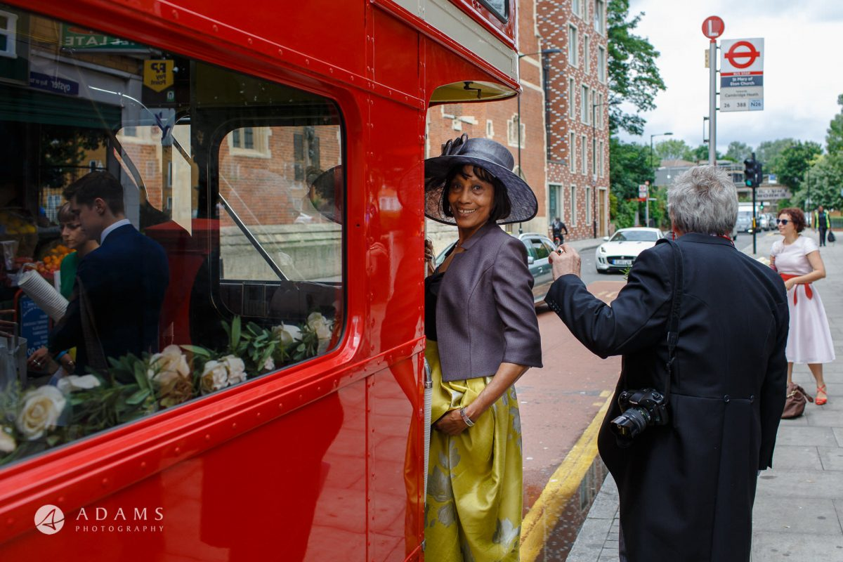 mother of the bride is getting on the red route-master bus in front of the st Mary of Eton church in hackney wick after the wedding ceremony