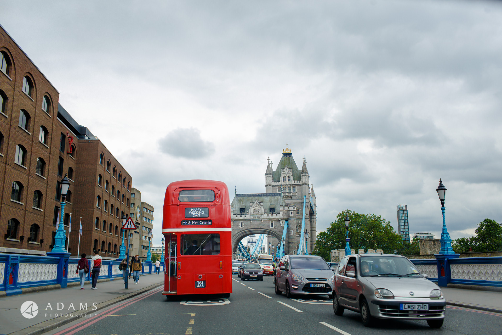 red bus with wedding guests approaching the tower bridge on away to Morden hall