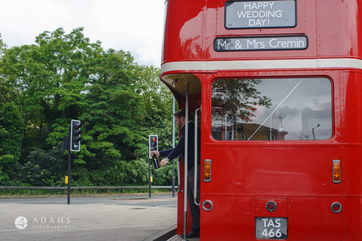 Guess is opening champagne on the bus picture taken by wedding photographer