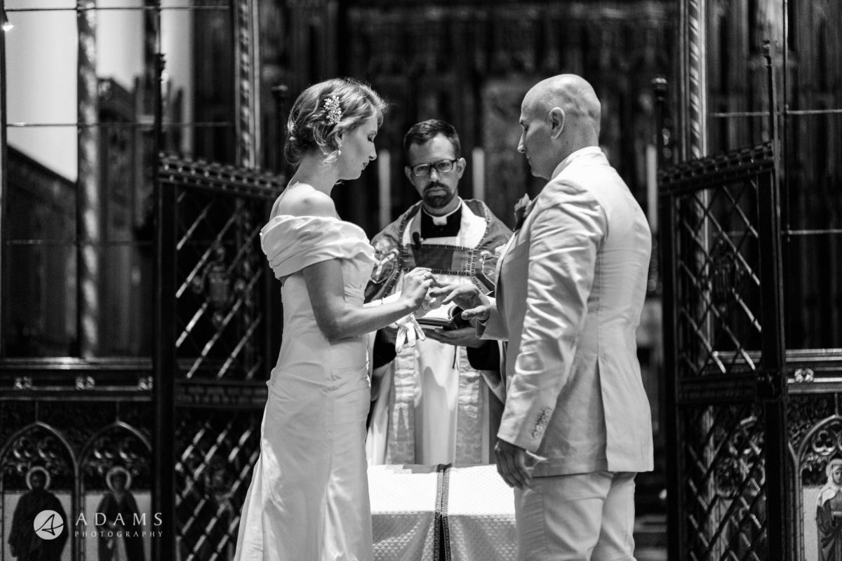 Black and White Wedding Photography bride is putting a ring on grooms finger