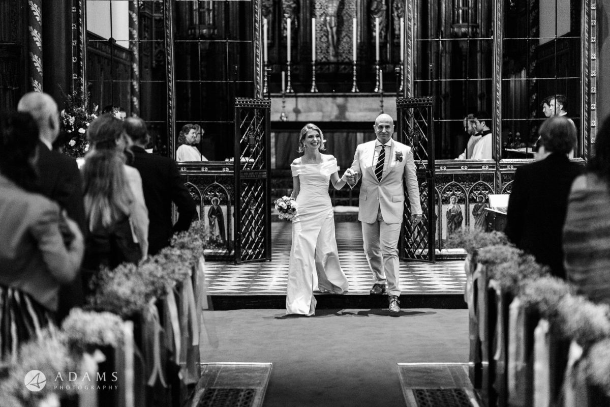 Black and White Wedding Photography couple walks out the church
