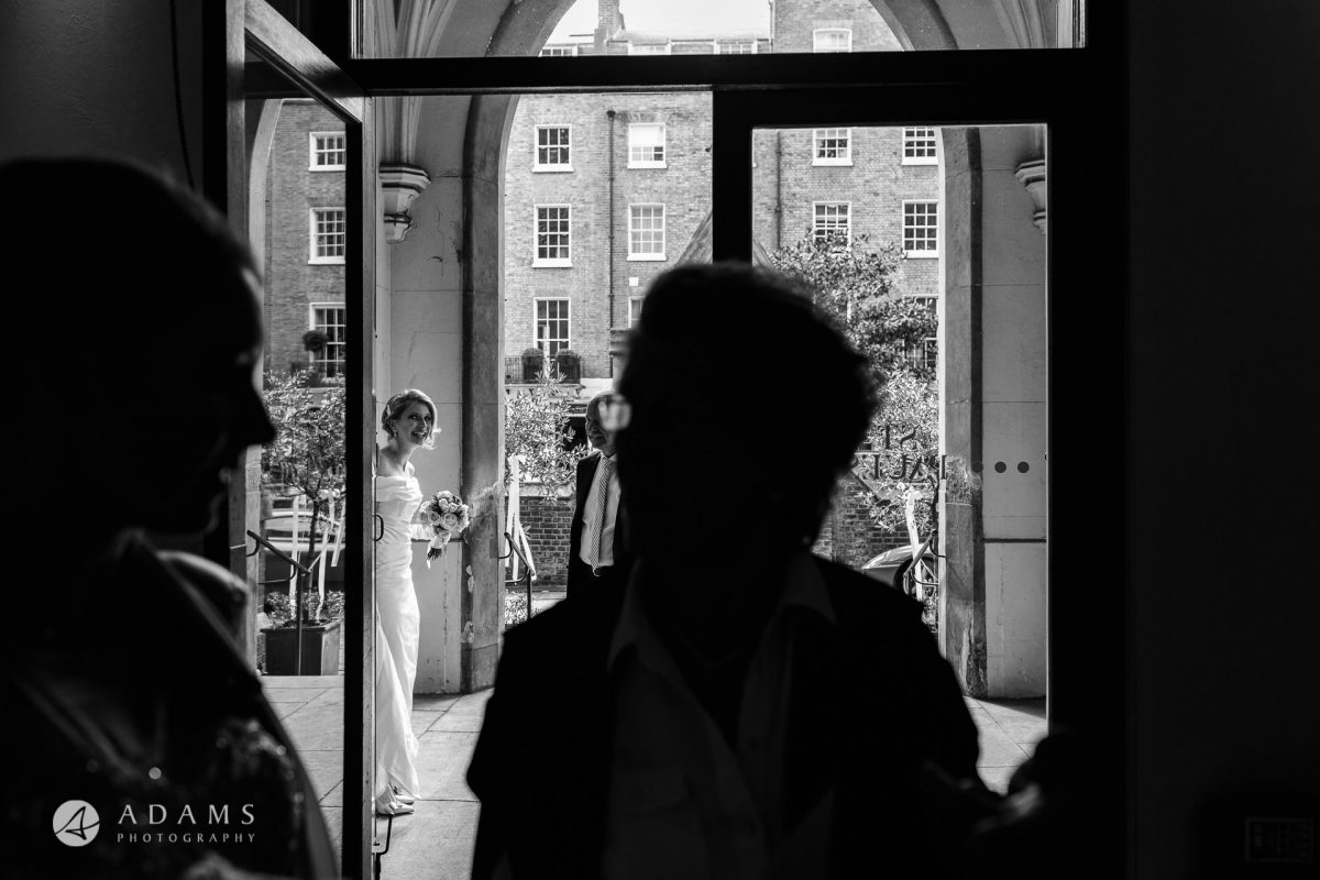 Black and White Wedding Photography bride by the entrance to the chhurch