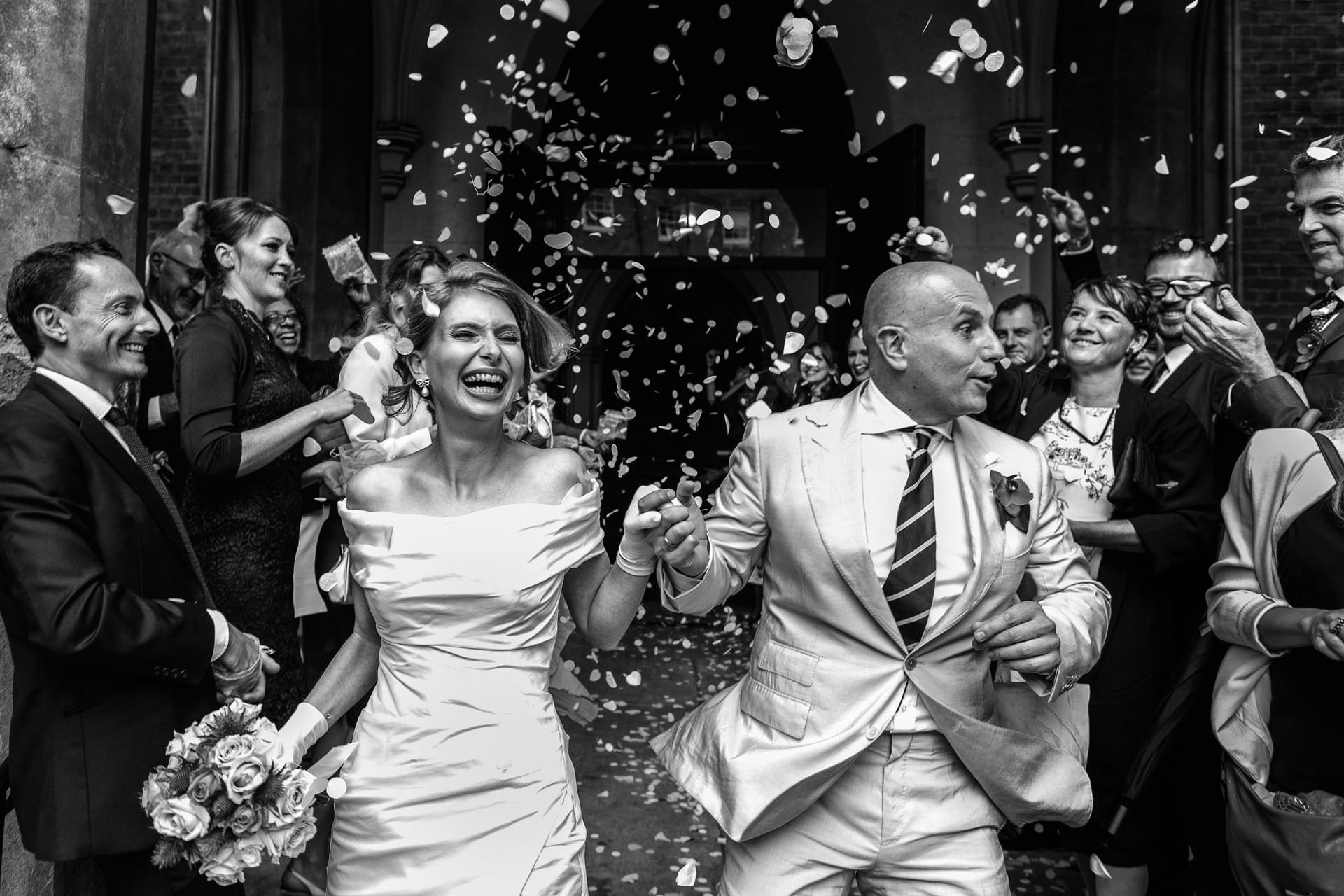 married couple running out from the church in Lonond showered with confetti and holding a big smile