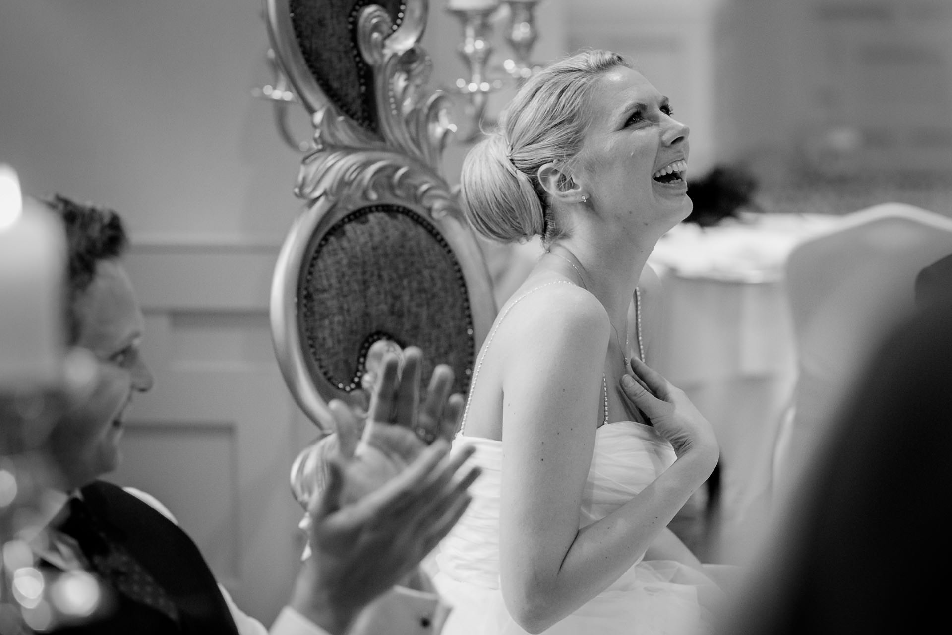 bride is laughing during the wedding speeches