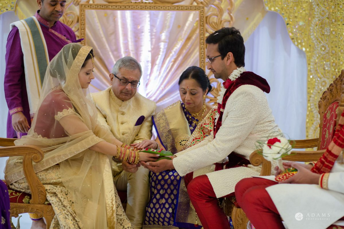 Hilton London Syon Park Asian Wedding couple hold hands at the mandap