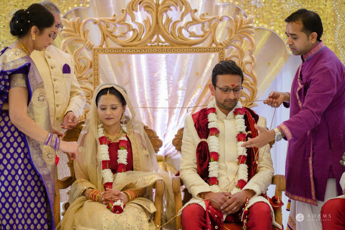 Hilton London Syon Park Asian Wedding couple sitting under mandap