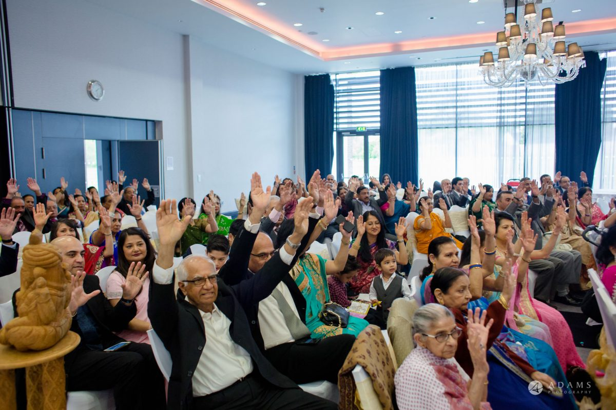 Hilton London Syon Park Asian Wedding guests raise their hands in the air