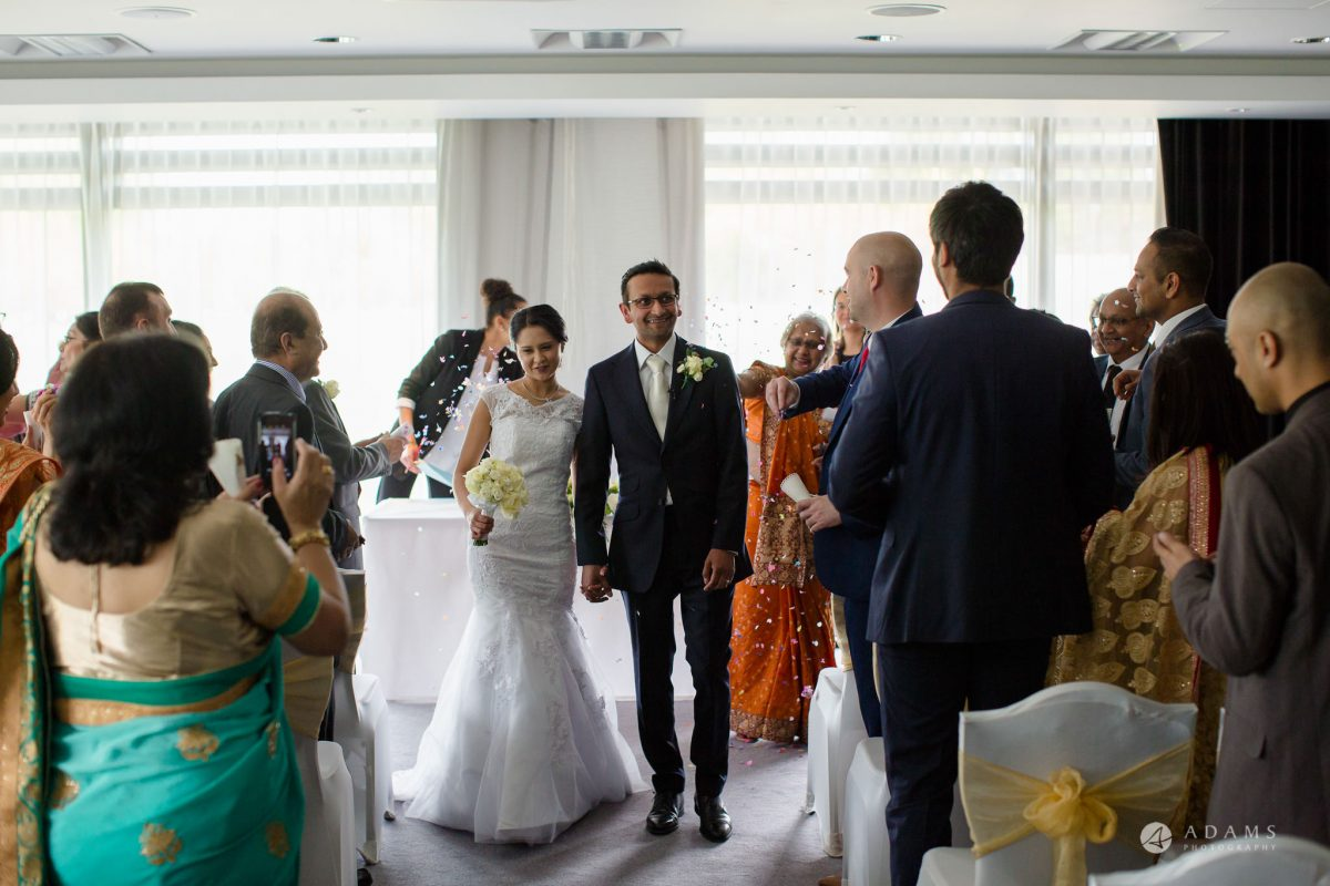 Hilton London Syon Park Asian Wedding the married couple leaving the ceremony