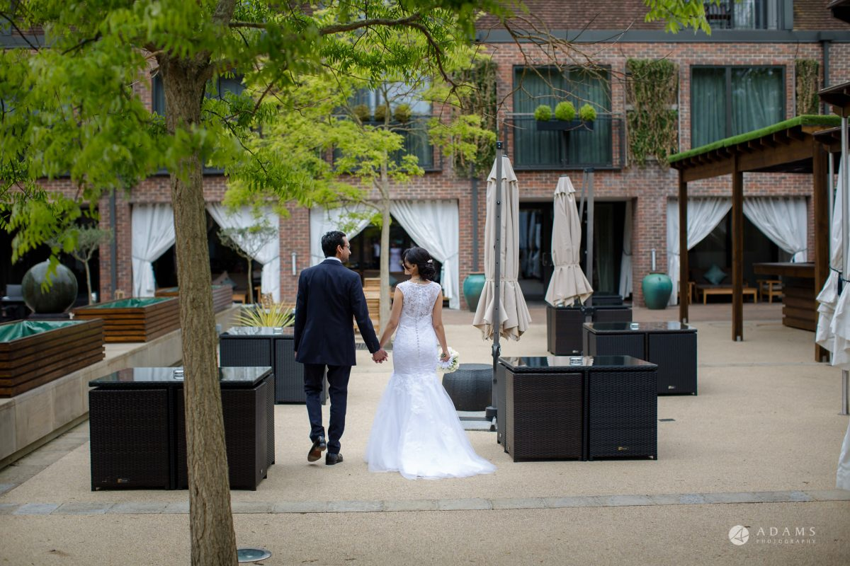 Hilton London Syon Park Asian Wedding bride and groom walk together holding hands