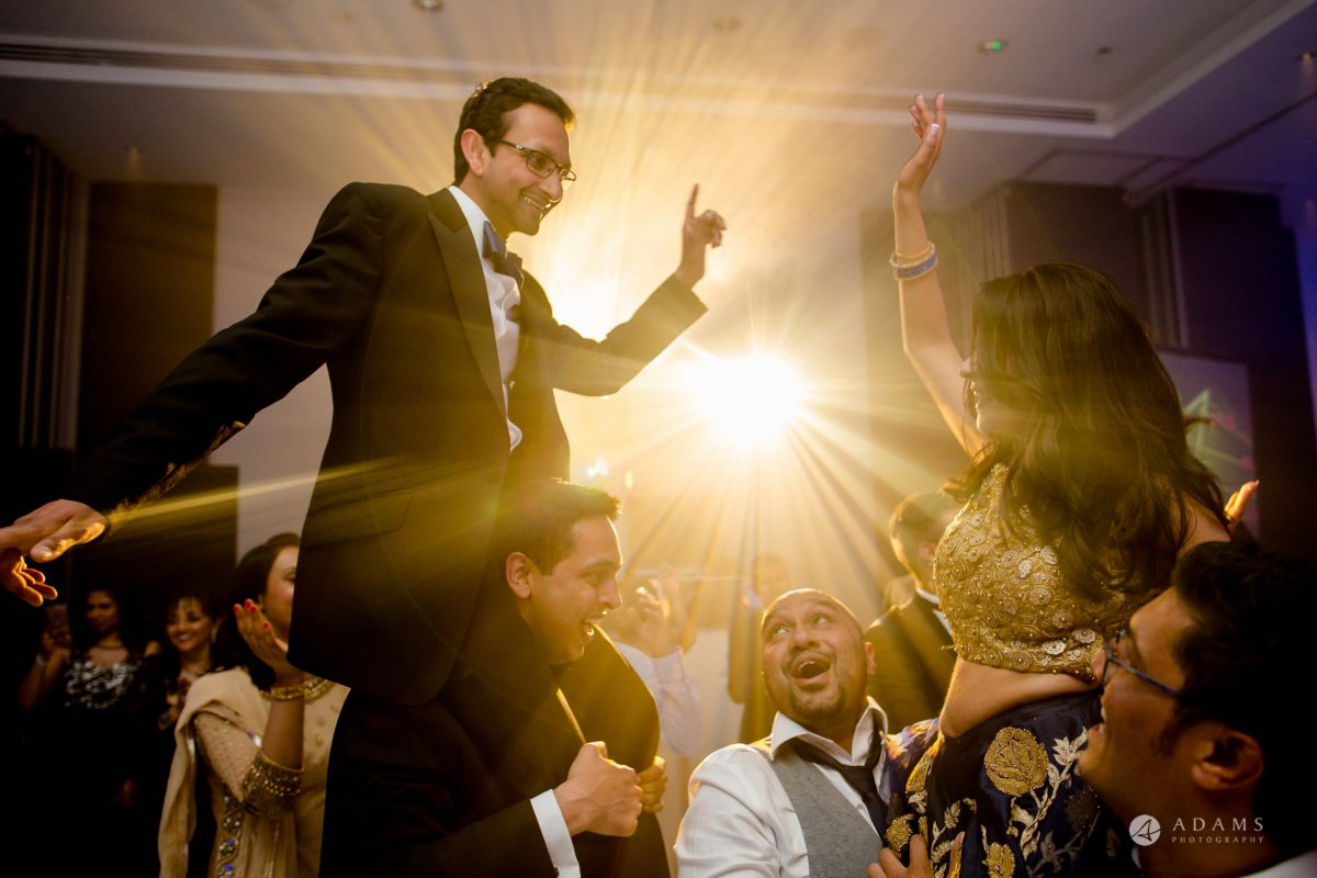 Hilton London Syon Park Asian Wedding bride and groom in the air dancing