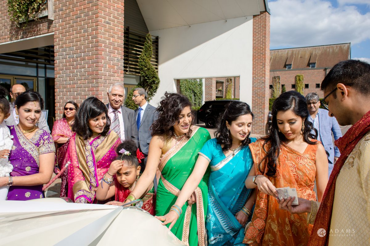 Hilton London Syon Park Asian Wedding bridesmaids haggling