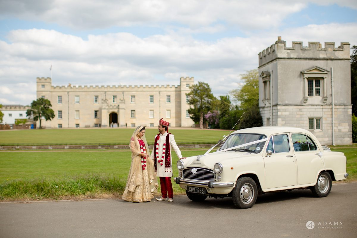 Hilton London Syon Park Asian Wedding the coupel pose in front of the venue