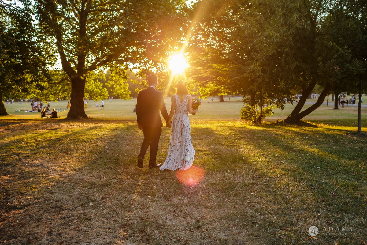 Clissold house wedding married couple walks away towards sun