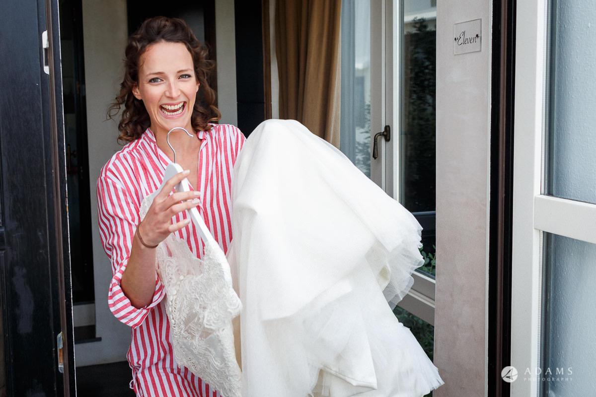 Spain Wedding Photographer bride carrying her dress