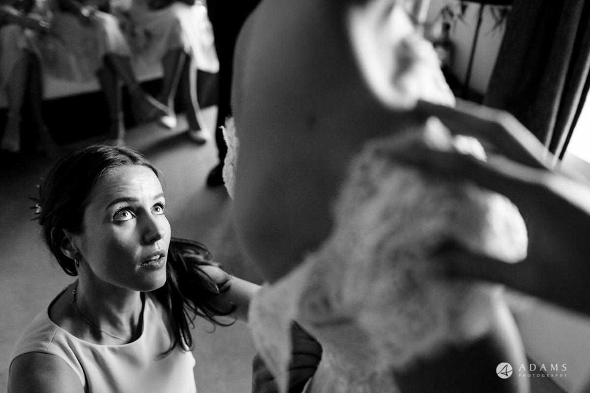 Spain Wedding photos bridesmaid helps with the dress