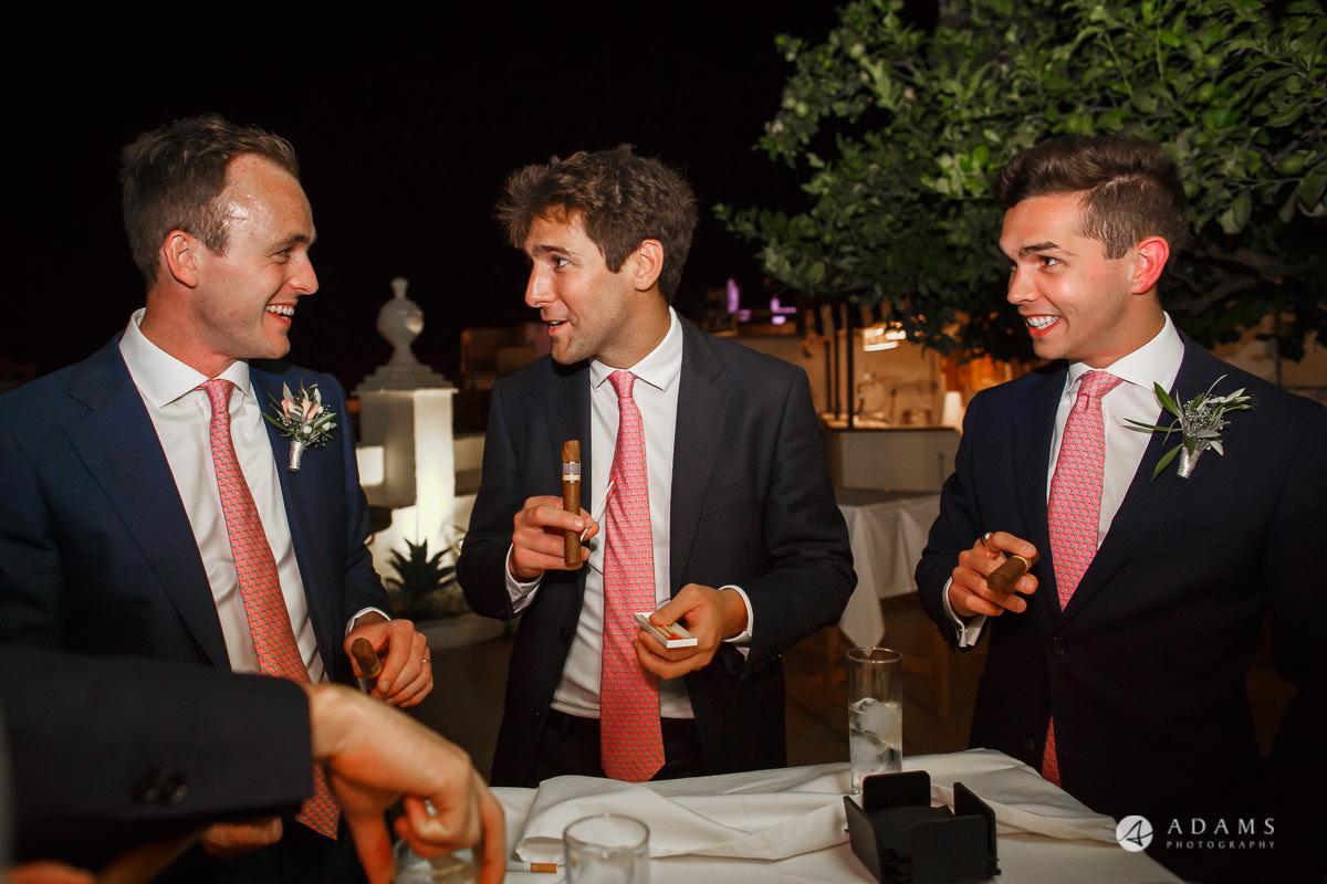 Spain Wedding Photographer groomand groomsmen having a cigar