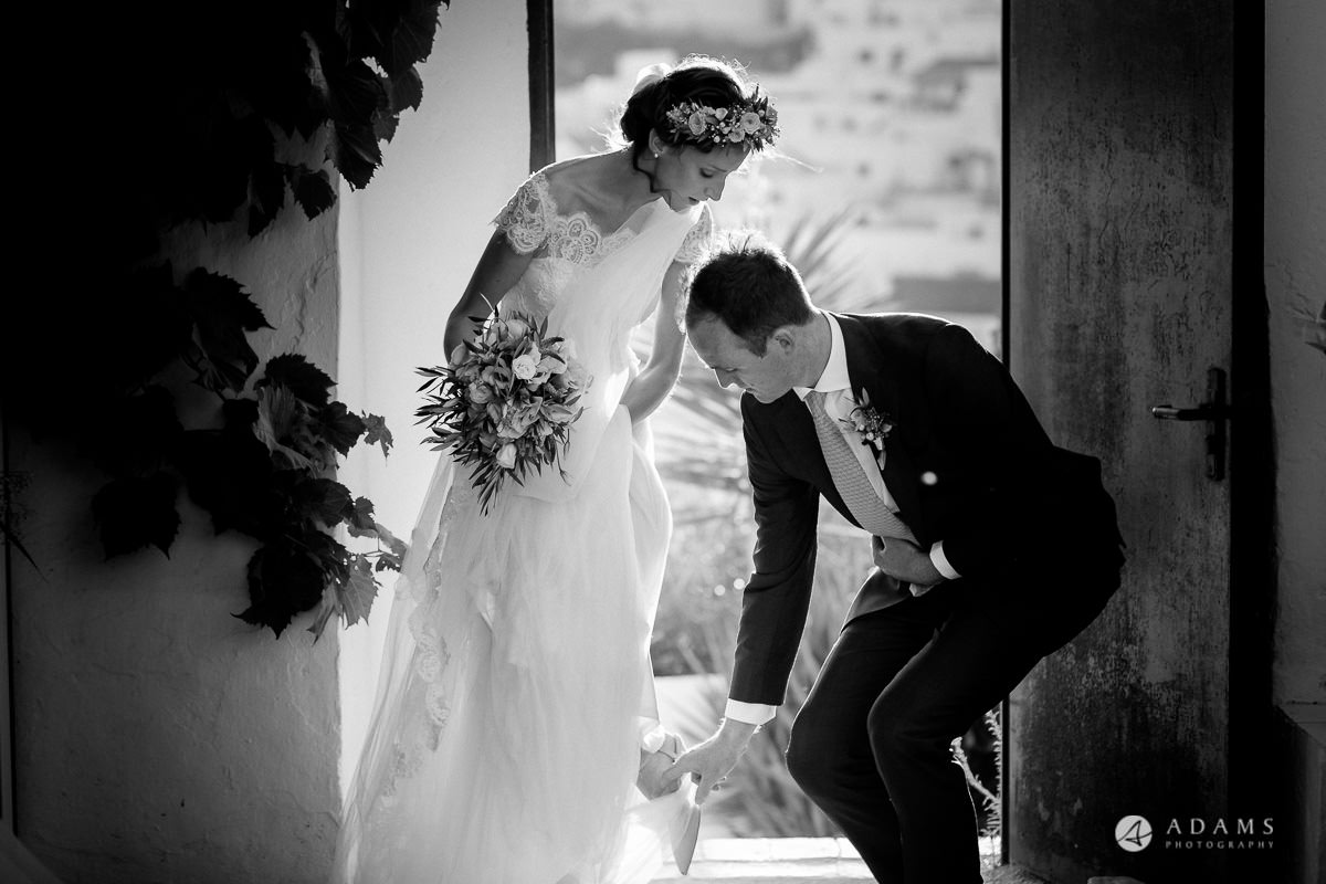 Destination Spain Wedding groom helps with the dress
