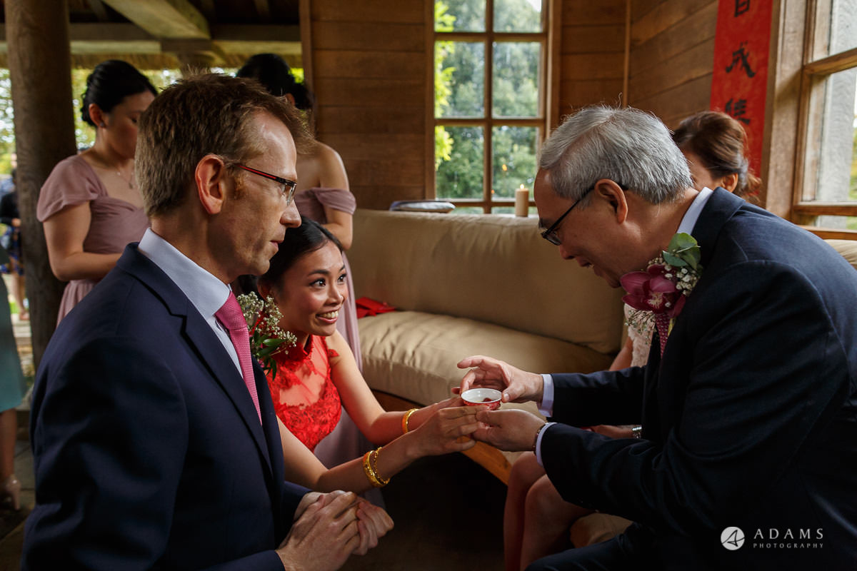 the lost orangery wedding chinese tea ceremony bride passing the tea to her father