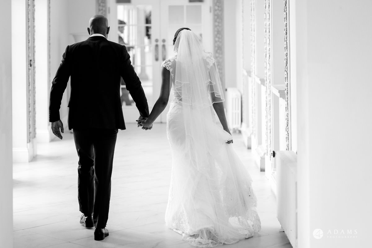 Froyle Park wedding couple holding hands and walking away