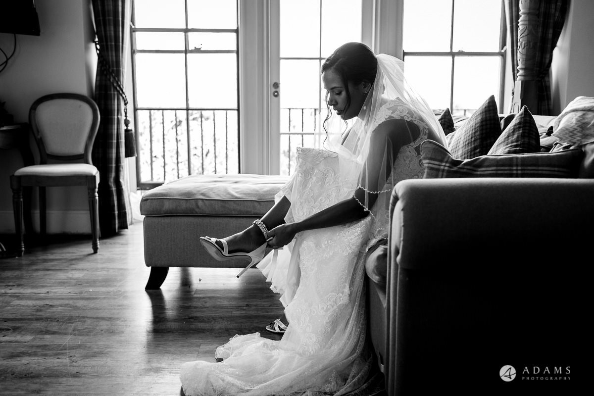 Froyle Park wedding bride puts on her shoes