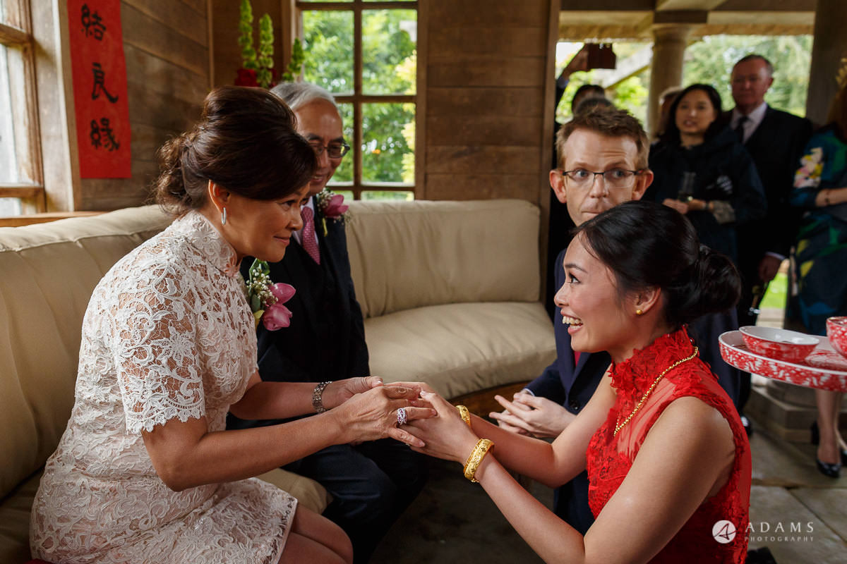 the lost orangery wedding chinese tea ceremony mother passing a gift to the bride