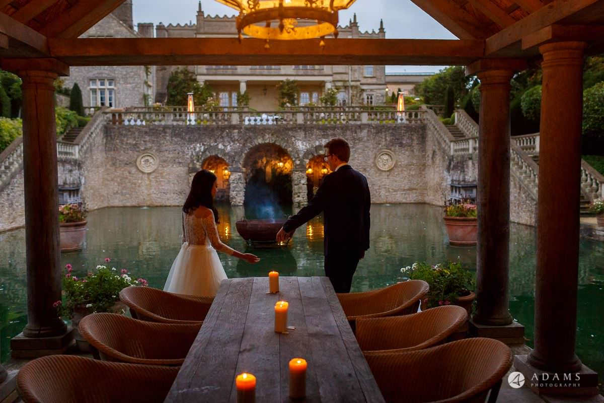 the lost orangery wedding the couple look at the venue standing front of the pond