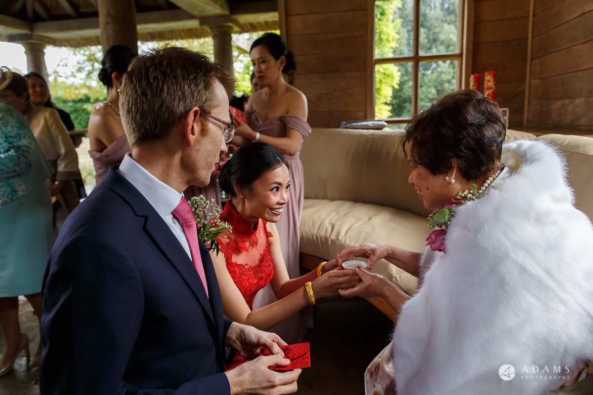 the lost orangery wedding chinese tea ceremony bride passing the tea to her mom